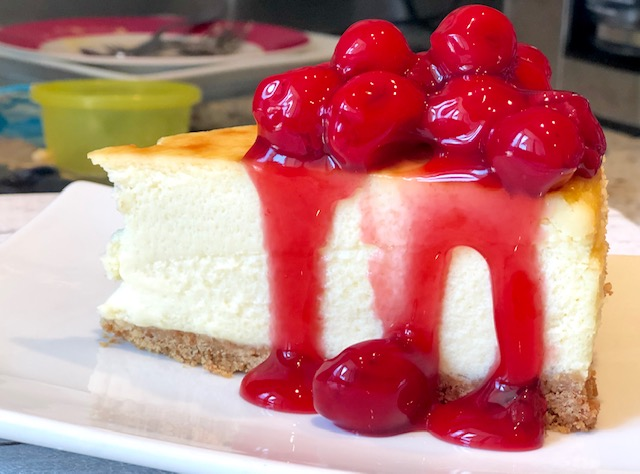 This image has an empty alt attribute; its file name is cherry-topping-cheesecake.jpg